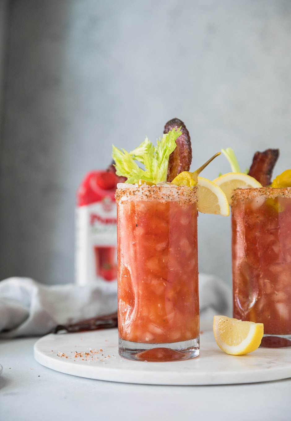 Forward facing shot of 2 bloody marys garnished with lemon, celery, and candied bacon with a carton of tomato juice in the background