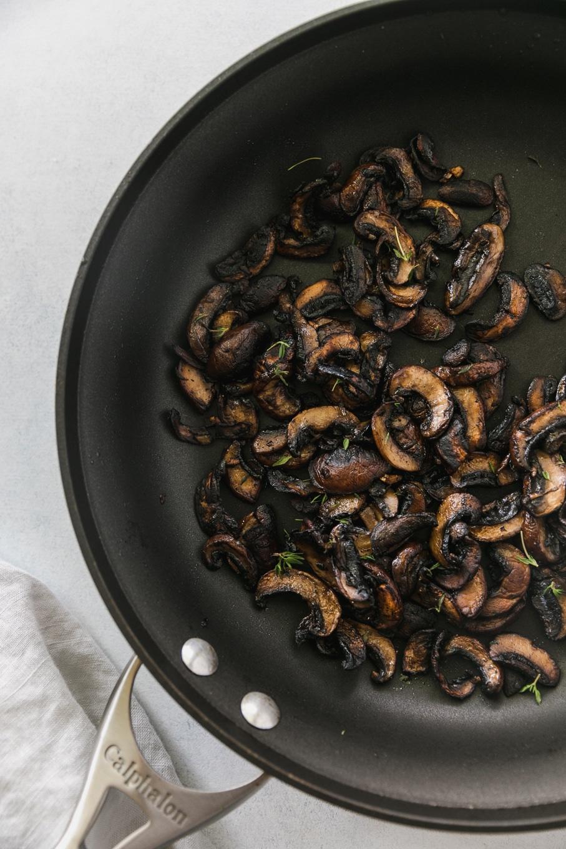Overhead shot of a black skillet filled with crispy sautéed mushrooms