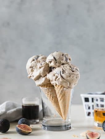 Forward facing shot of two ice cream cones standing up in a glass with a glass of bourbon and a shot glass of maple syrup next to it, as well as fresh figs