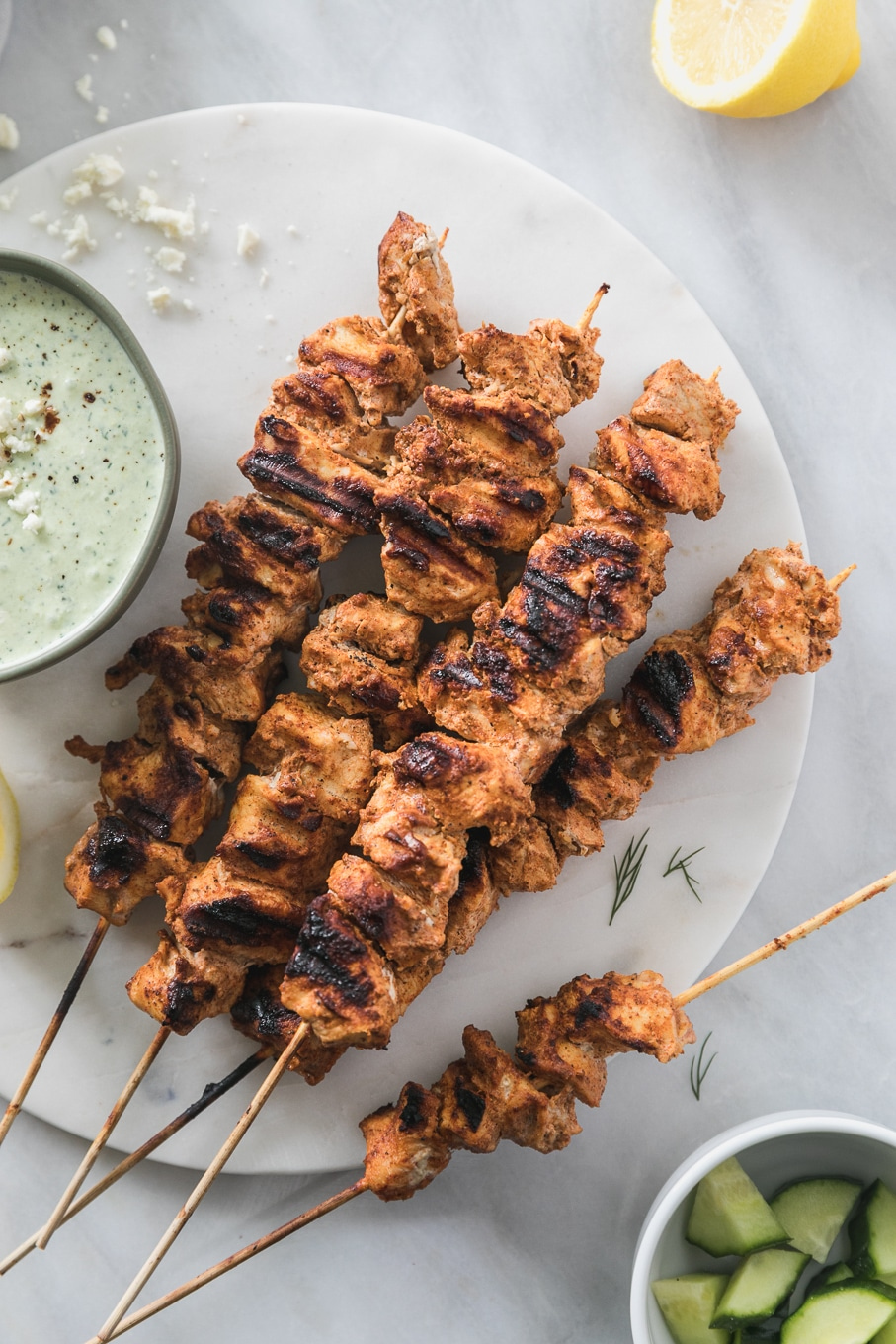 Overhead shot of a pile of grilled chicken skewers with a bowl of lemony feta tzatziki next to it
