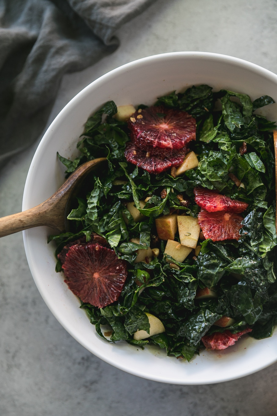 Overhead close up shot of a mixing bowl filled with kale salad with blood oranges and apples in it, as well as a wooden spoon