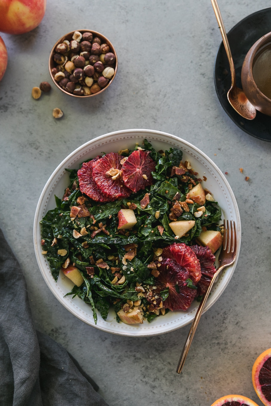 Overhead shot of a bowl of kale salad with blood oranges, apples, chopped bacon, and hazelnuts with a gold fork resting in the bowl and a ramekin of hazelnuts above it as well as a bowl of dressing on a small plate with a gold spoon