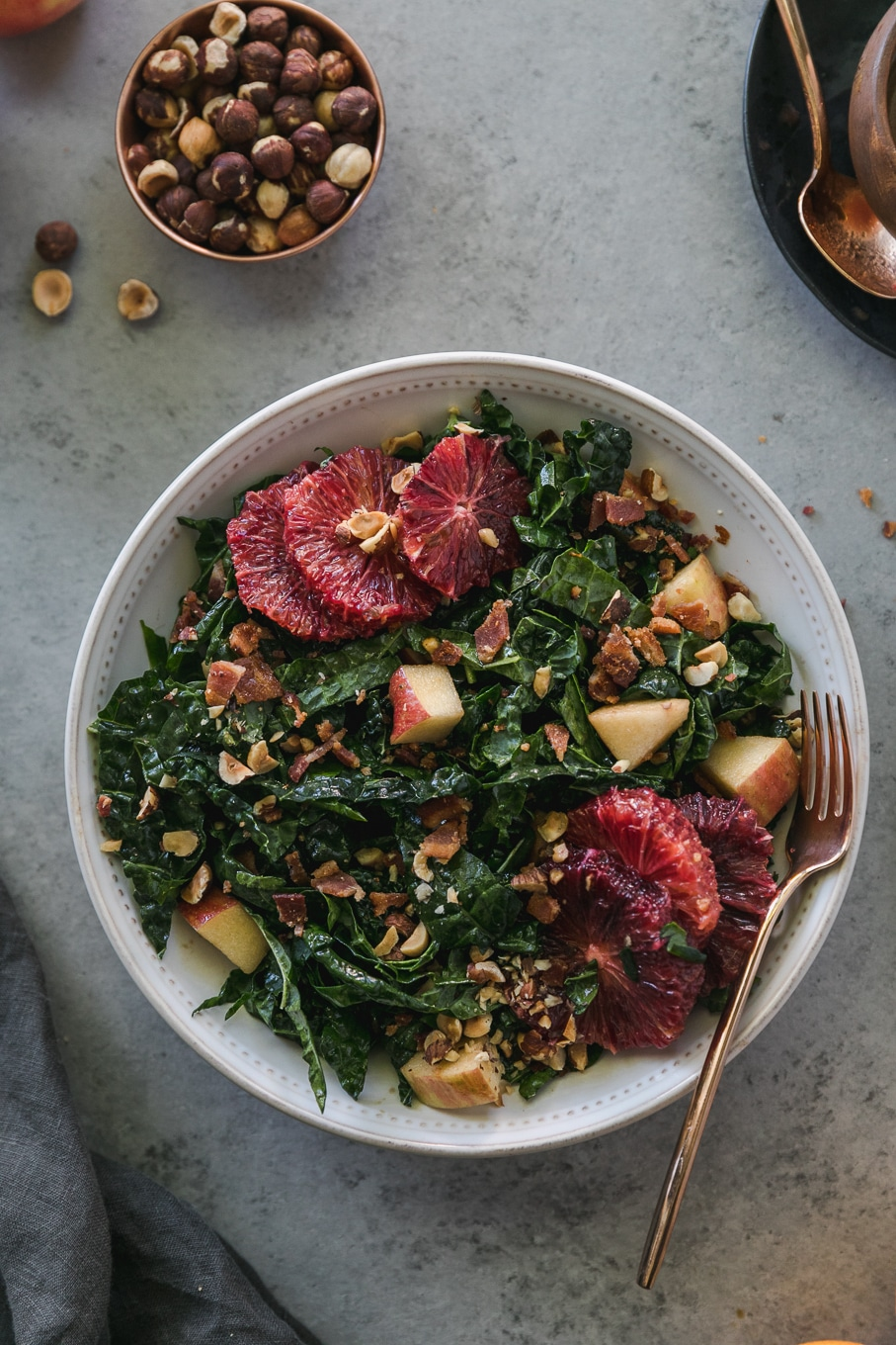 Overhead close up shot of a bowl of kale salad with blood oranges, apples, chopped bacon, and hazelnuts