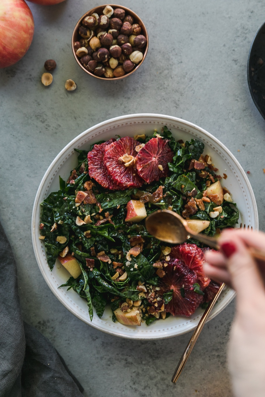 Overhead shot of a bowl of kale salad with blood oranges, apples, chopped bacon, and hazelnuts with a hand drizzling dressing on it with a gold spoon