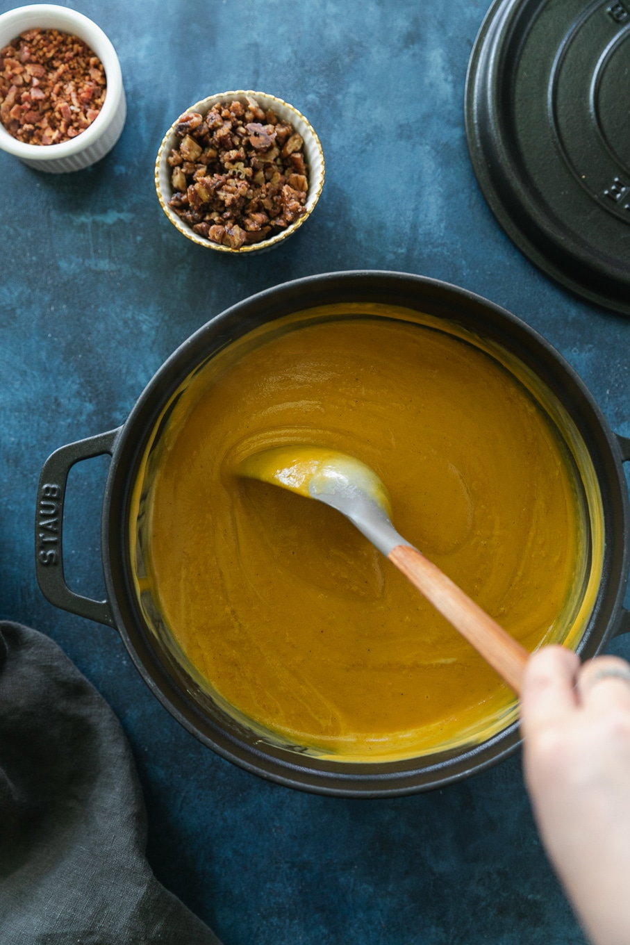 Overhead shot of a black dutch oven filled with creamy sweet potato soup being stirred with a spoon with a grey top and wooden handle