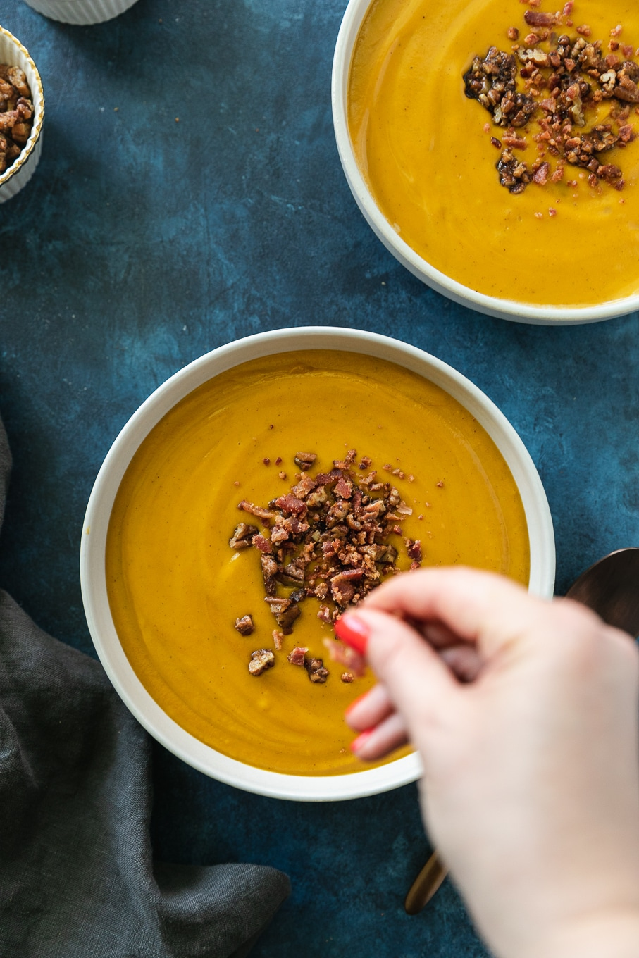Overhead shot of a bowl of creamy sweet potato soup being sprinkled with bacon and maple pecan crunch