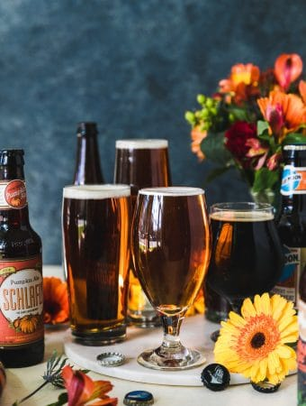 Forward facing shot of beer glasses filled with different colors of beer and beer bottles next to it with a vase of flowers in the background and a yellow flower in the foreground