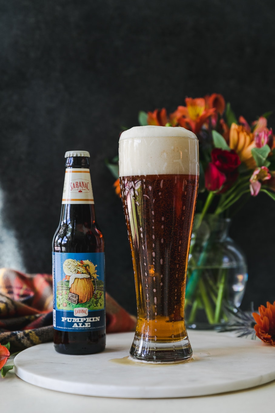 Forward facing shot of a beer glass filled with beer and a beer bottle next to it with a vase of flowers in the background and orange flowers scattered around