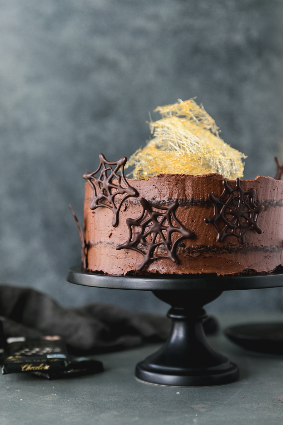 Forward facing shot of a chocolate cake with dark chocolate spider webs on it and a spun sugar cobweb on top on a black cake stand