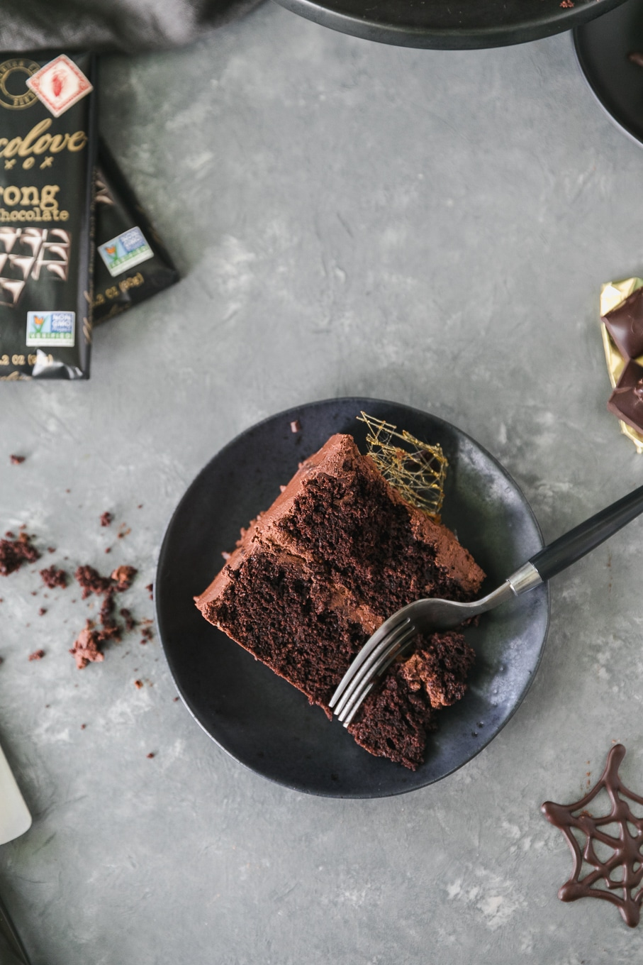 Overhead shot of a piece of chocolate cake on a black plate with a fork taking a bite out of it