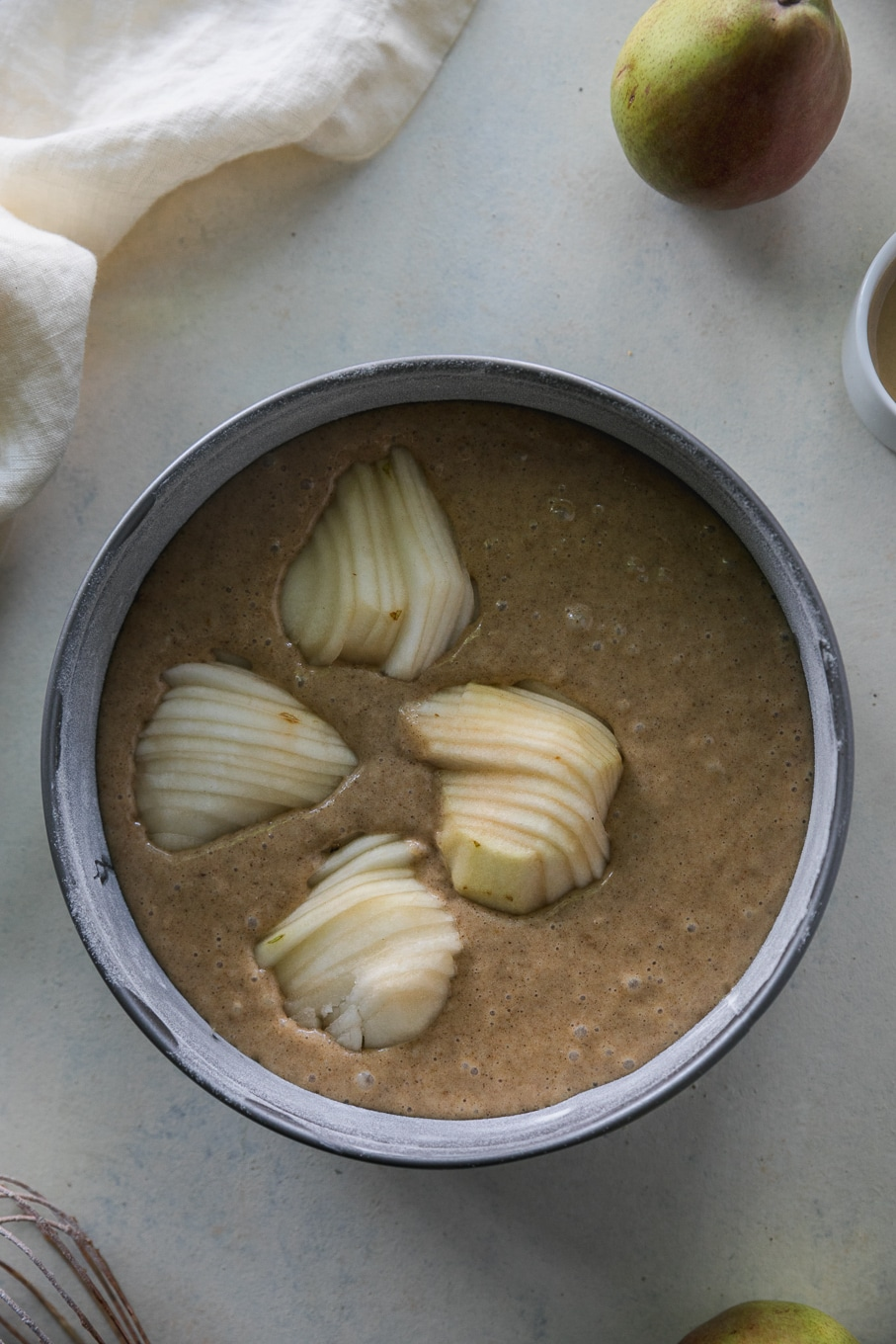 Overhead shot of a springform pan filled with batter and sliced pears on top