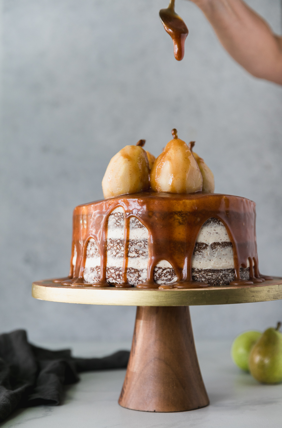 Forward facing shot of a cake on a wooden and gold pedestal topped with poached pears