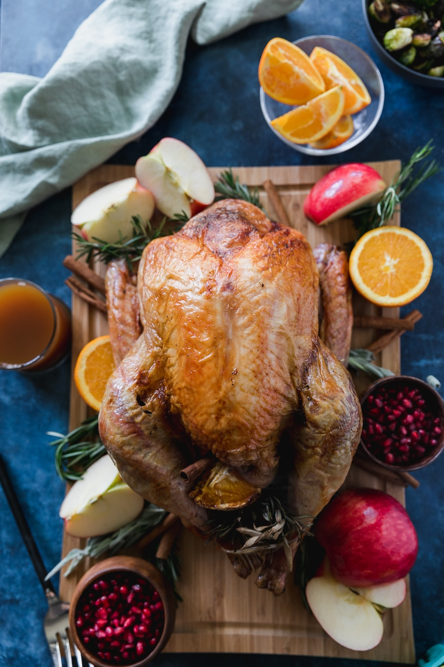 Overhead shot of a roasted whole turkey on a wooden cutting board on a blue background, surrounded by apples, pomegranate arils, oranges, and fresh herbs