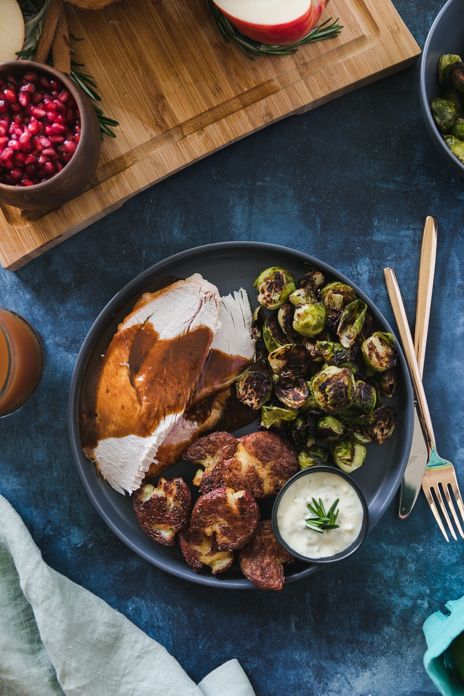 Overhead shot of a plate with turkey and gravy, roasted brussels, roasted smashed potatoes, and aioli against a blue background