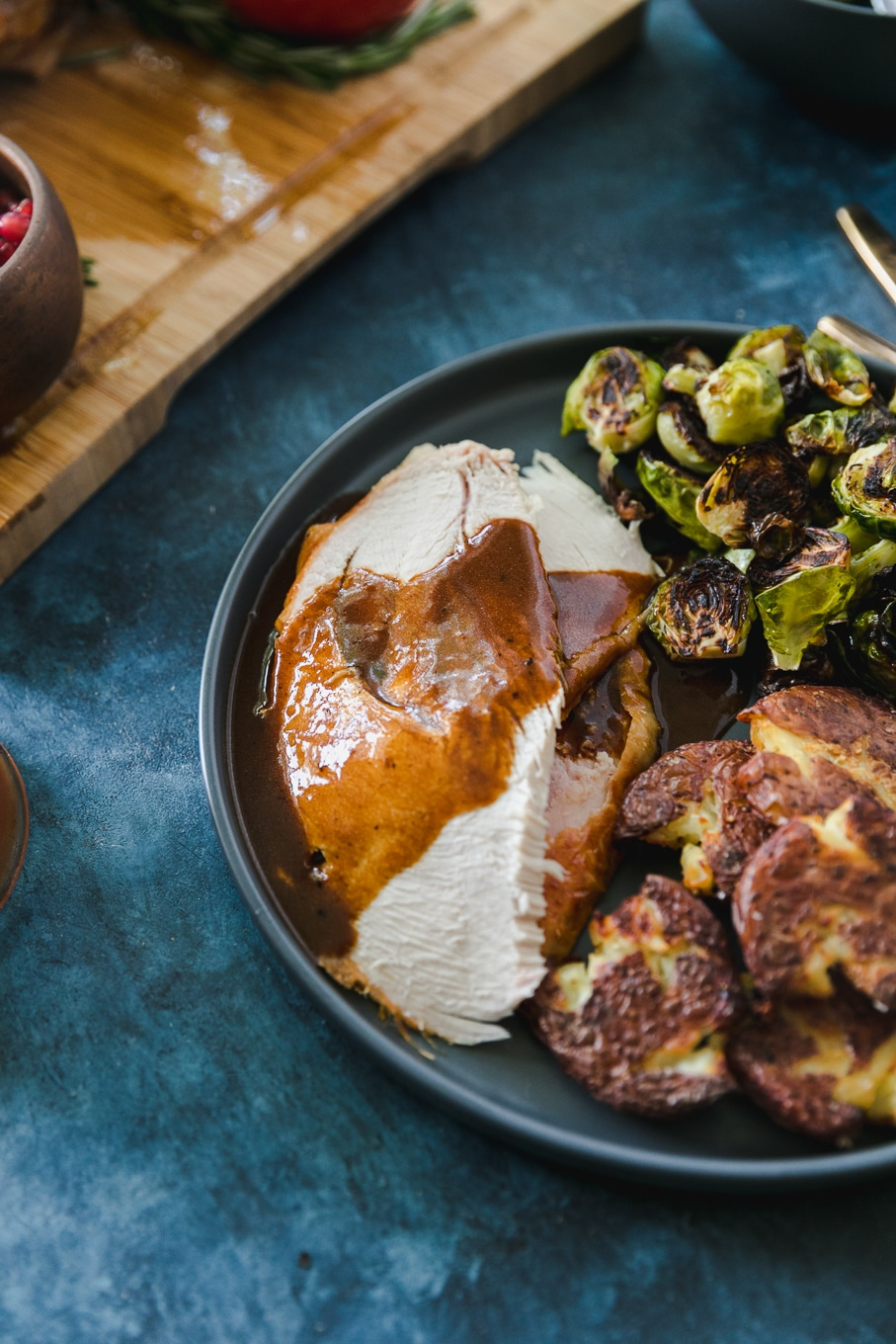 Close up shot of a plate of sliced turkey and gravy, roasted smashed potatoes, and roasted brussels against a blue background