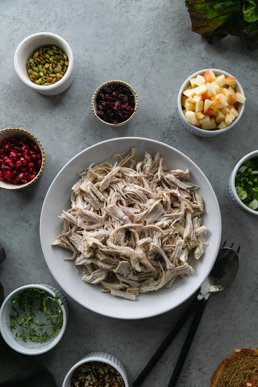 Overhead shot of a bowl of shredded chicken surrounded by bowls of chopped apples, pomegranate arils, dried cranberries, toasted pepitas, thyme, and scallions on a grey background