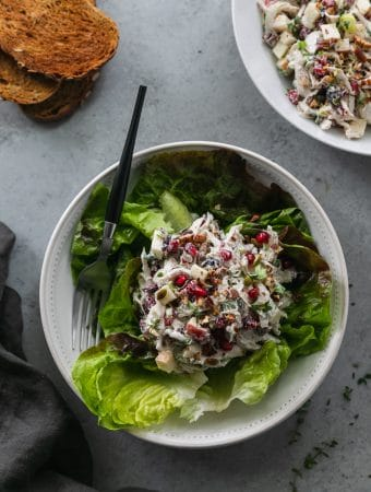 Overhead shot of a pile of chicken salad resting on a bed of green butter lettuce leaves in a white bowl with a fork resting in the bowl, and a stack of toasted bread in the top left