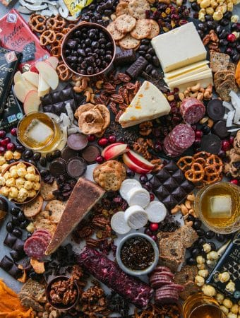 Overhead shot of a chocolate and bourbon cheeseboard with apples, cranberries, crackers, pretzels, caramel corn, assorted cheeses, salami, and candy