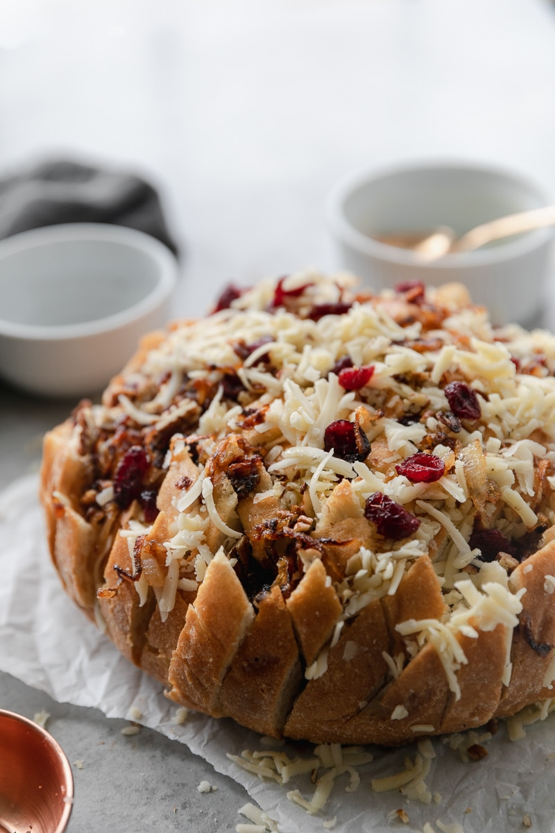 Close up shot of a loaf of bread stuffed with shredded cheese, caramelized onions, cranberries, and pecans