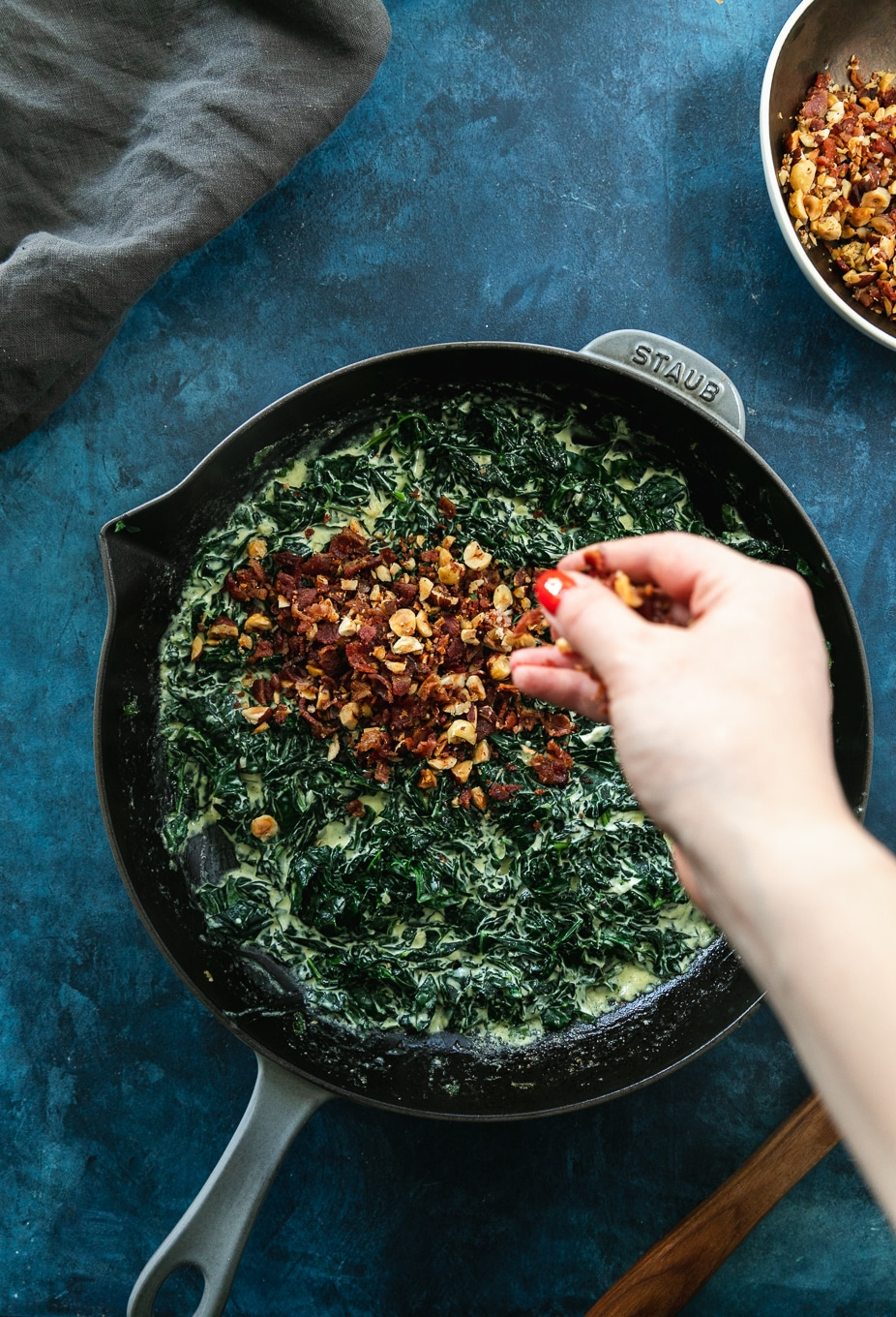 Overhead shot of a cast iron skillet filled with creamed kale and a hand sprinkling hazelnut bacon crunch on top