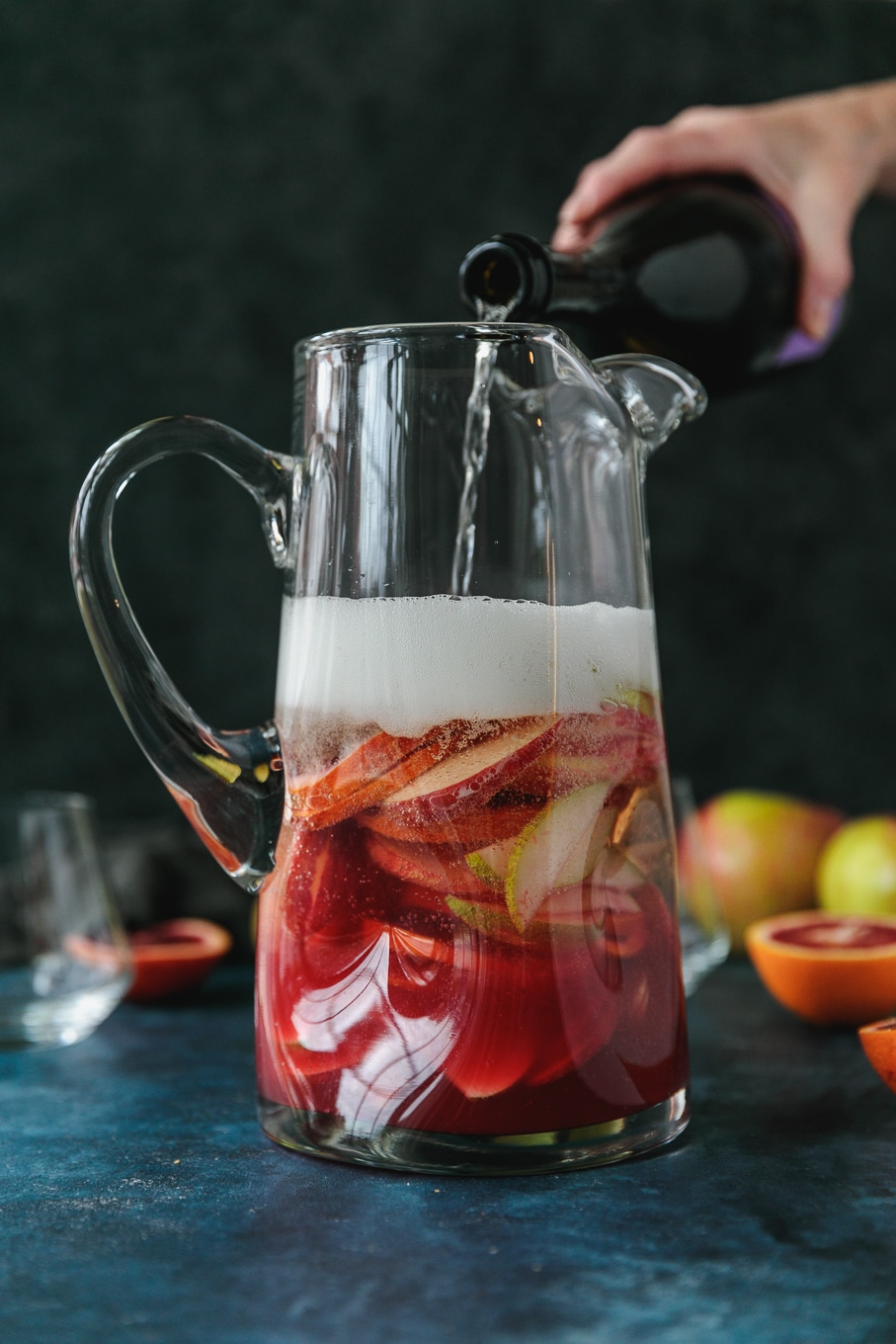 Forward facing shot of a pitcher filled with pink sparkling blood orange sangria filled with sliced apples, pears, and blood oranges with a bottle of champagne being poured into it