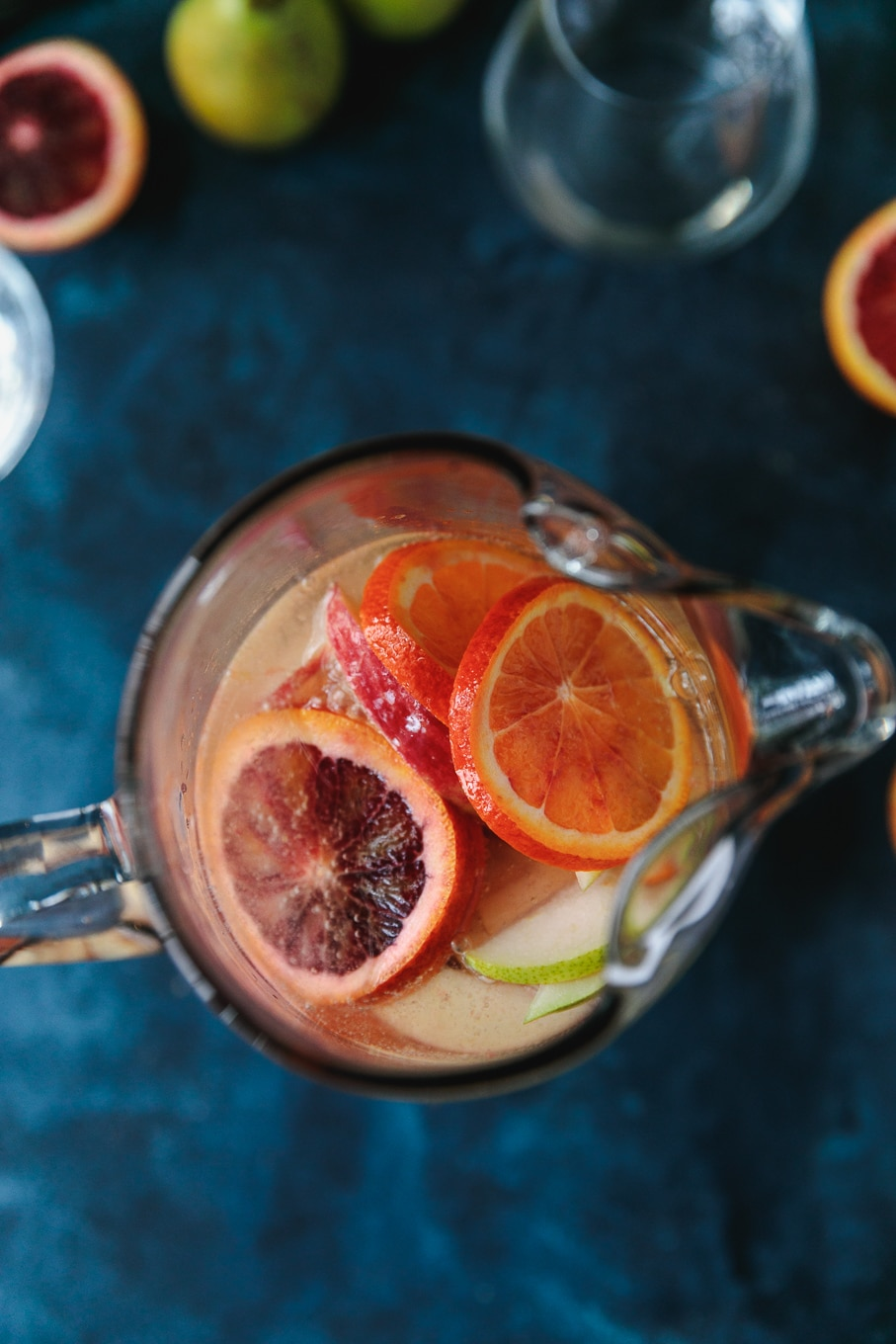 Overhead shot of a pitcher filled with pink sparkling blood orange sangria filled with sliced apples, pears, and blood oranges