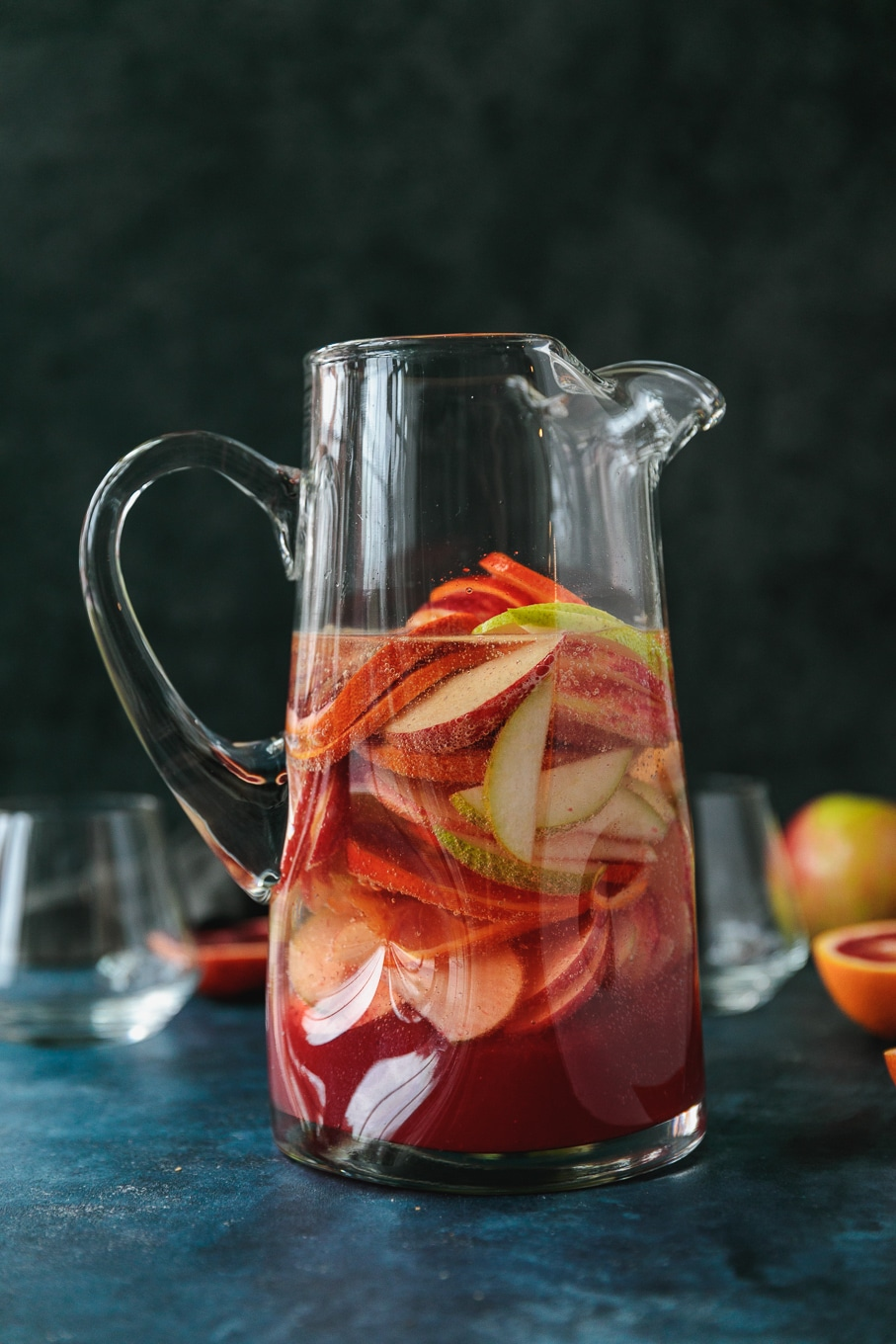 Forward facing shot of a pitcher filled with pink sparkling blood orange sangria filled with sliced apples, pears, and blood oranges