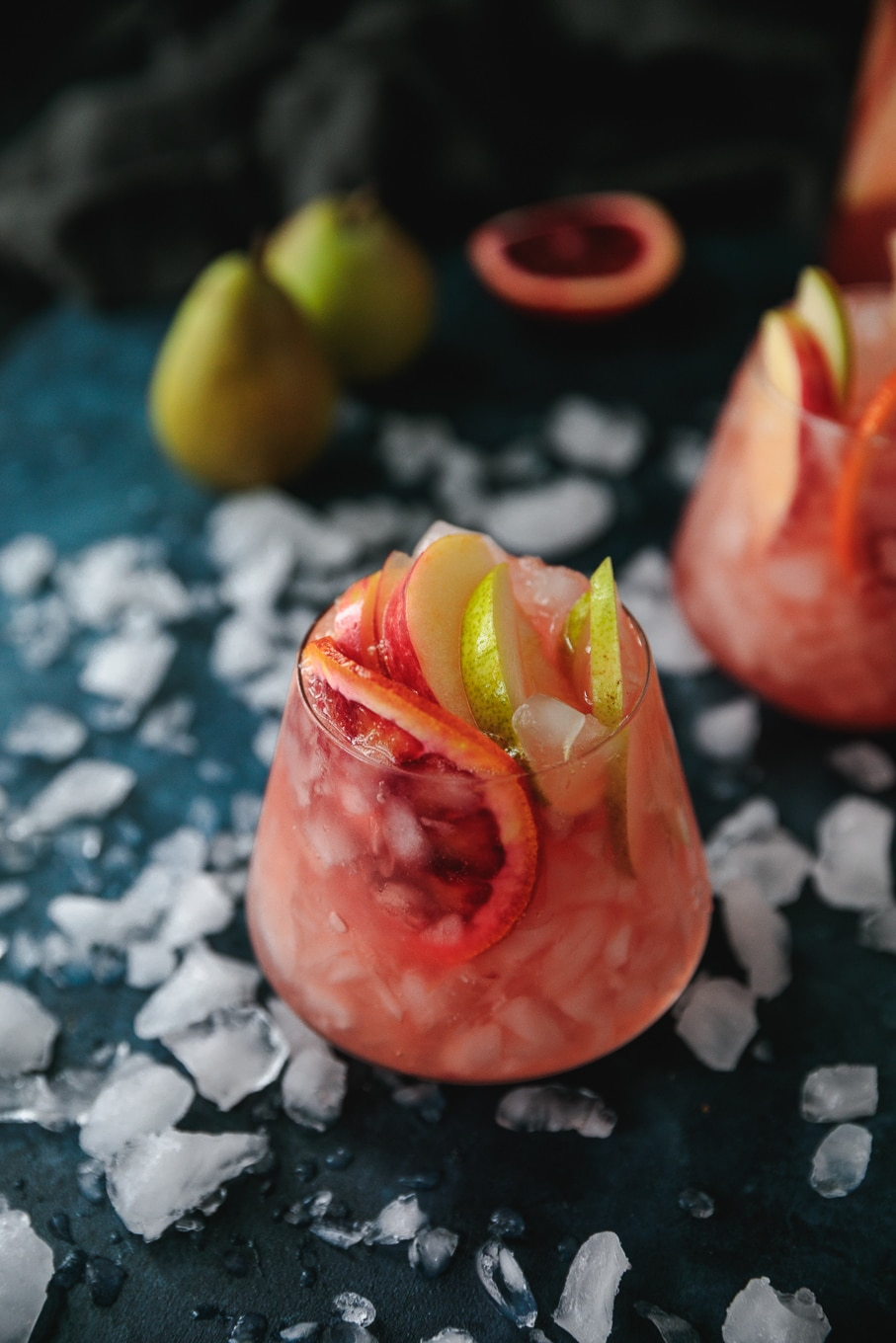 Close up shot of a glass of pink sparkling blood orange sangria with sliced apples, pears, and blood oranges sticking out against a blue background scattered with crushed ice
