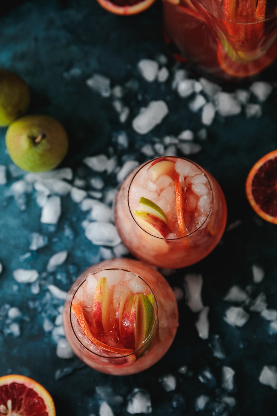 Overhead shot of two pink sparkling blood orange cocktails garnished with pears, apples, and blood orange slices, against a dark blue background with crushed ice scattered around