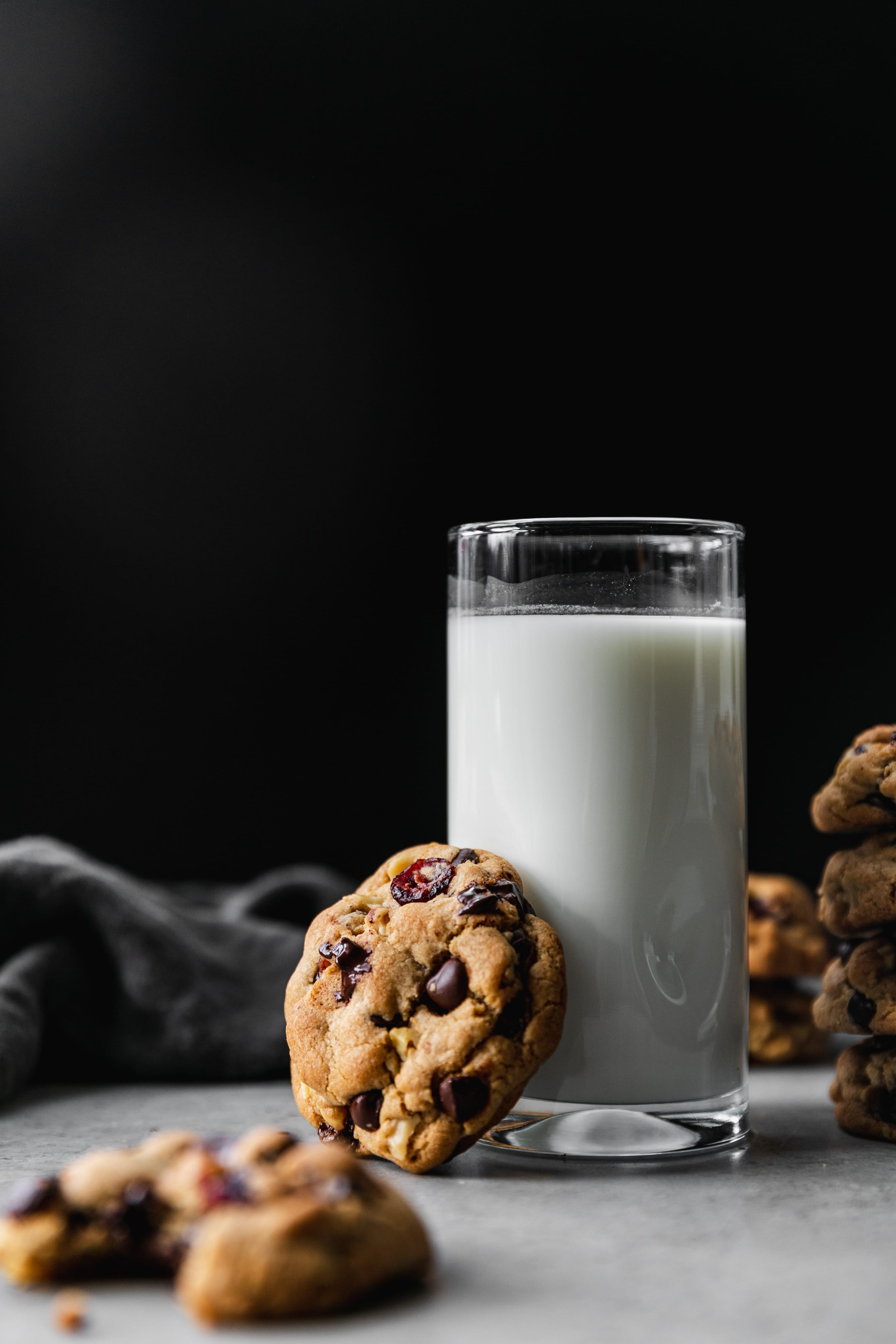 Shot of a glass of milk against a black background with a dark chocolate cranberry walnut cookie resting up against it and a stack of cookies next to it