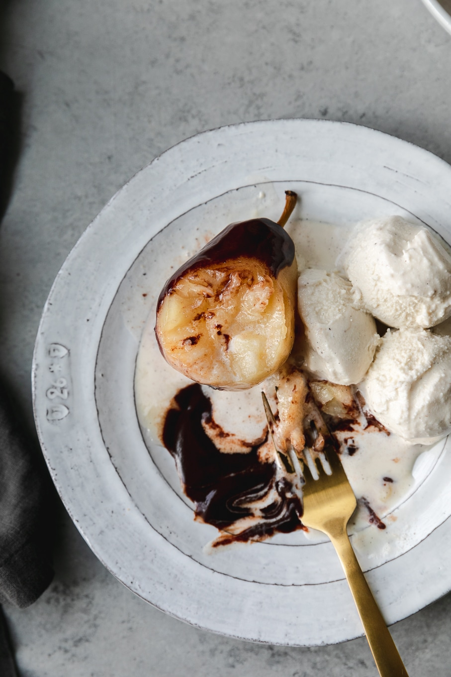 Overhead shot of a poached pear being eaten with chocolate fudge sauce and ice cream on a white plate with a gold fork