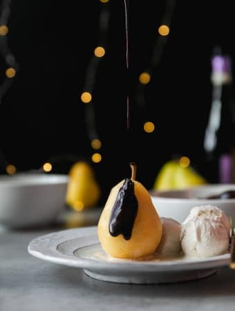 Forward facing shot of a poached pear being drizzled with dark chocolate fudge sauce and ice cream on the side on a white plate with a black background and twinkle lights behind it