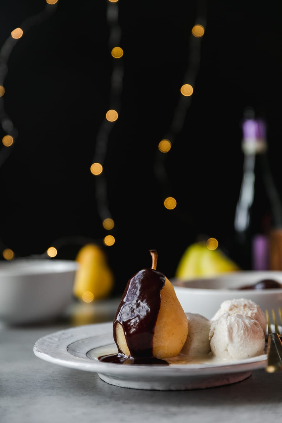 Forward facing shot of a poached pear drizzled with dark chocolate fudge sauce and ice cream on the side on a white plate with a black background and twinkle lights behind it