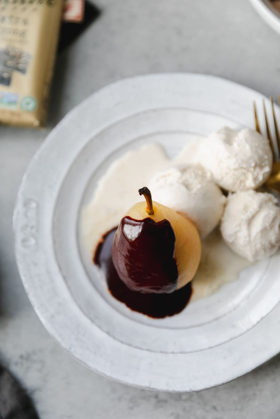 Overhead shot of a poached pear covered in chocolate fudge sauce and ice cream on the side on a white plate with a gold fork