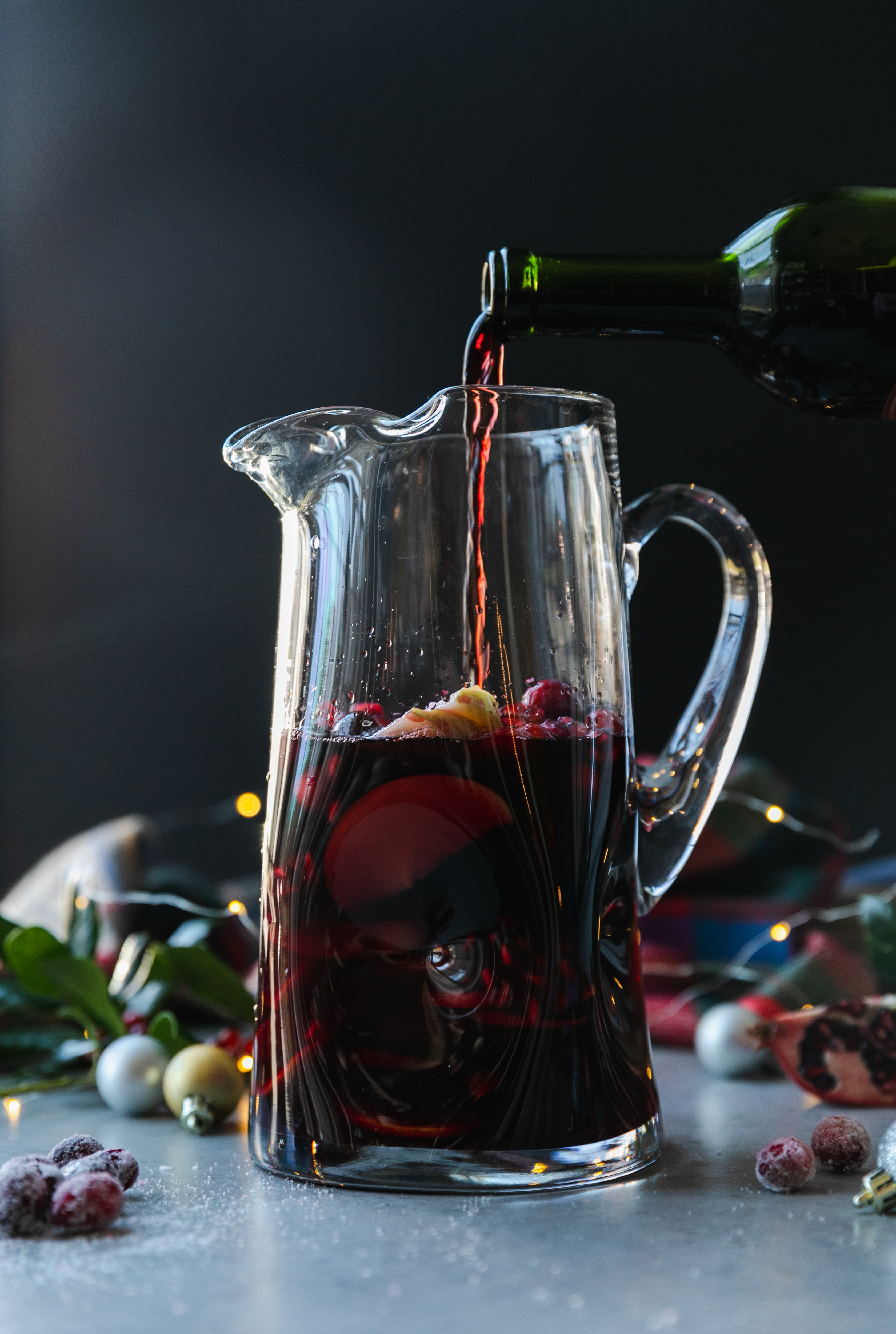 Forward facing shot of a glass pitcher filled with red sangria and red wine being poured into it with christmas ornaments, a plaid scarf, and twinkle lights in the background