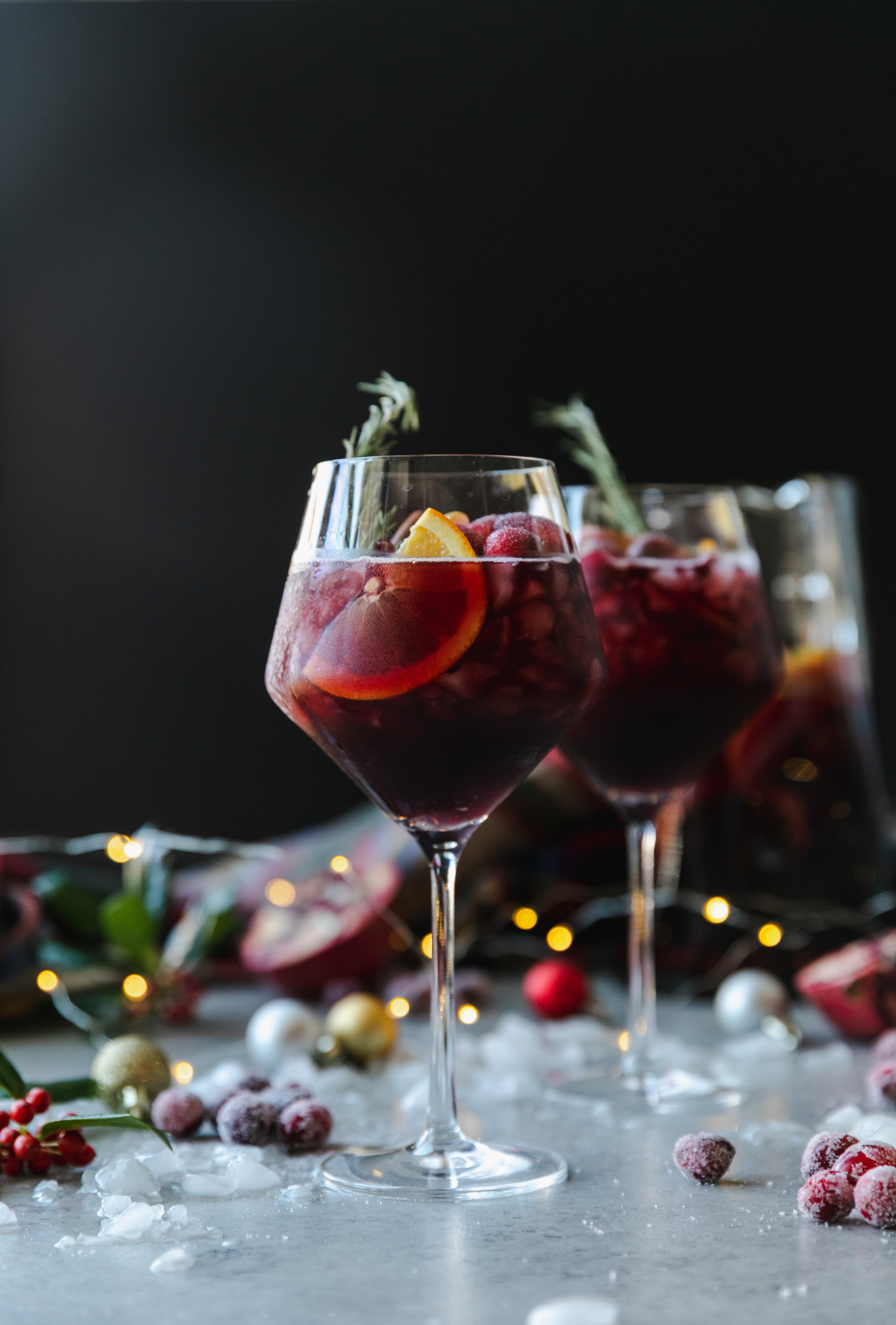 Forward facing shot of a wine glass filled with red sangria, garnished with a rosemary sprig, with another glass behind it, with crushed ice, christmas ornaments, a plaid scarf, a pitcher of sangria, and twinkle lights in the background