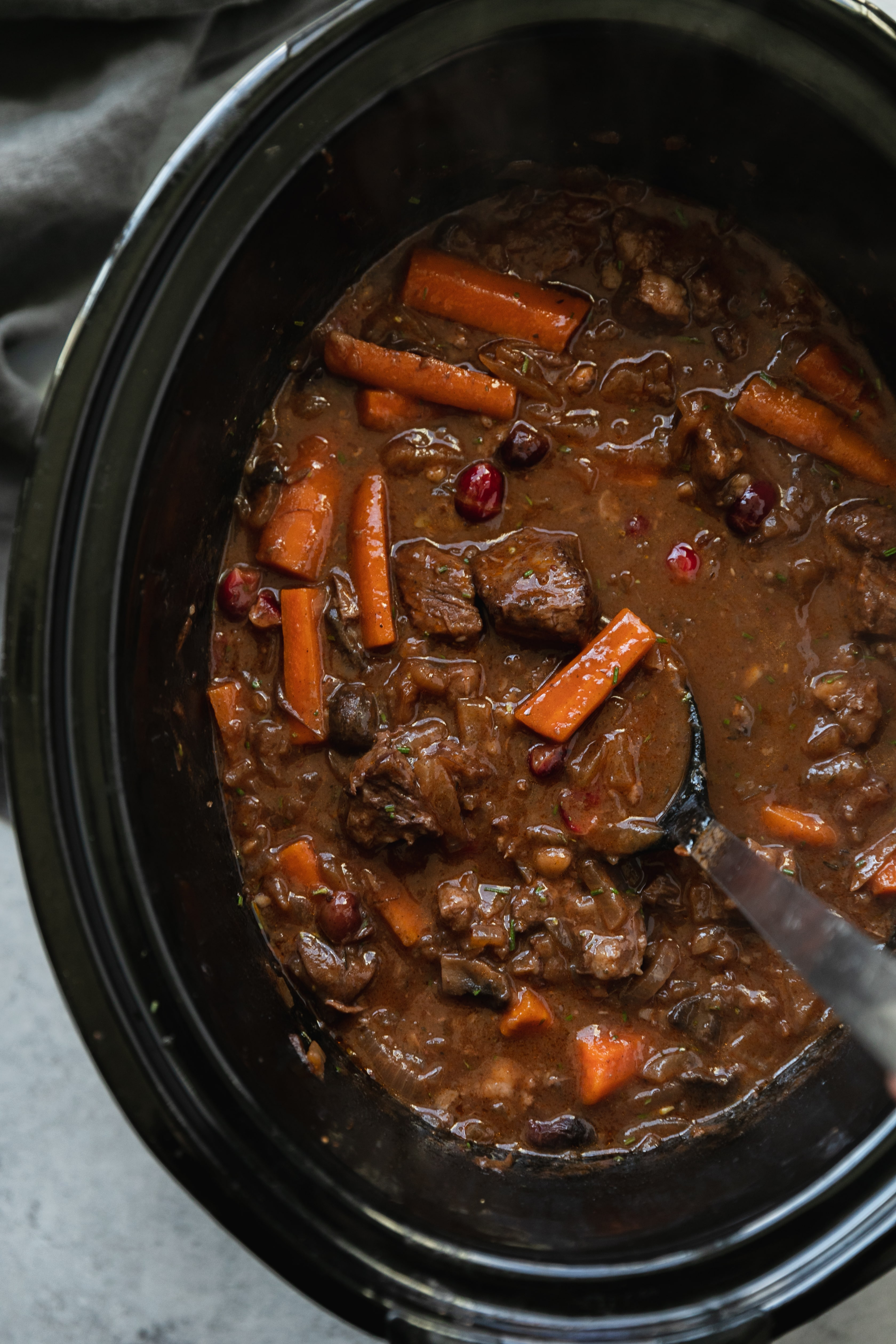 Overhead shot of a slow cooker filled with cranberry beef stew and a spoon resting in it