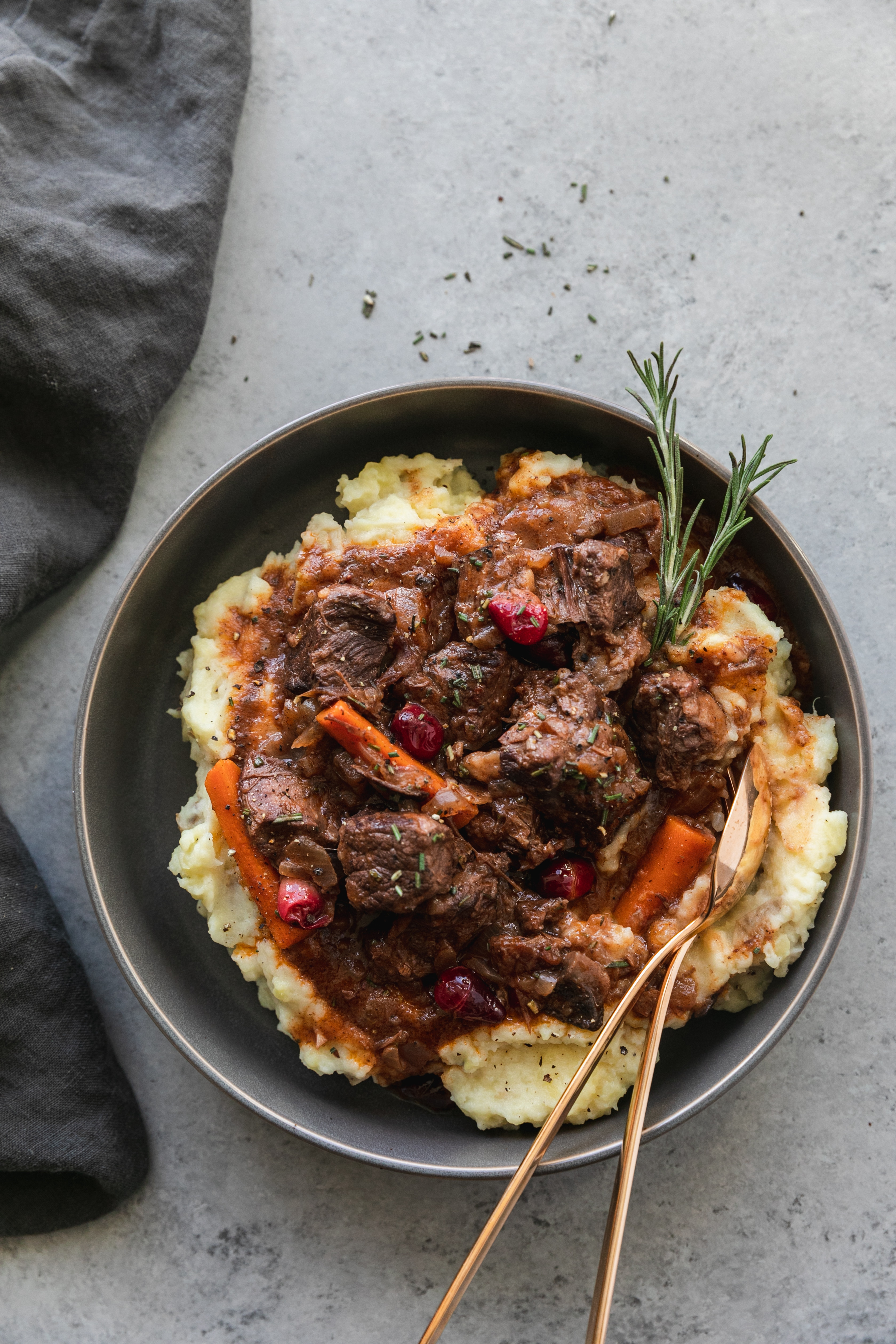 Overhead shot of a bowl of mashed potatoes topped with beef stew and a rosemary sprig with two gold spoons in the bowl