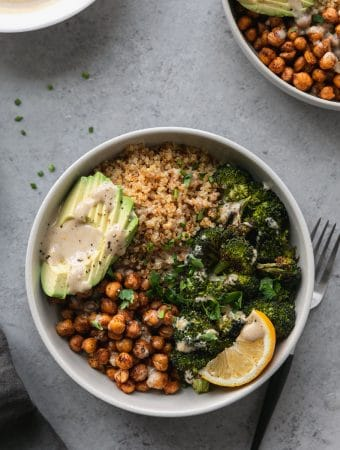 Overhead shot of a bowl with quinoa, chickpeas, roasted broccoli, sliced avocado, a lemon wedge, and tahini sauce with a black and silver fork next to the bowl