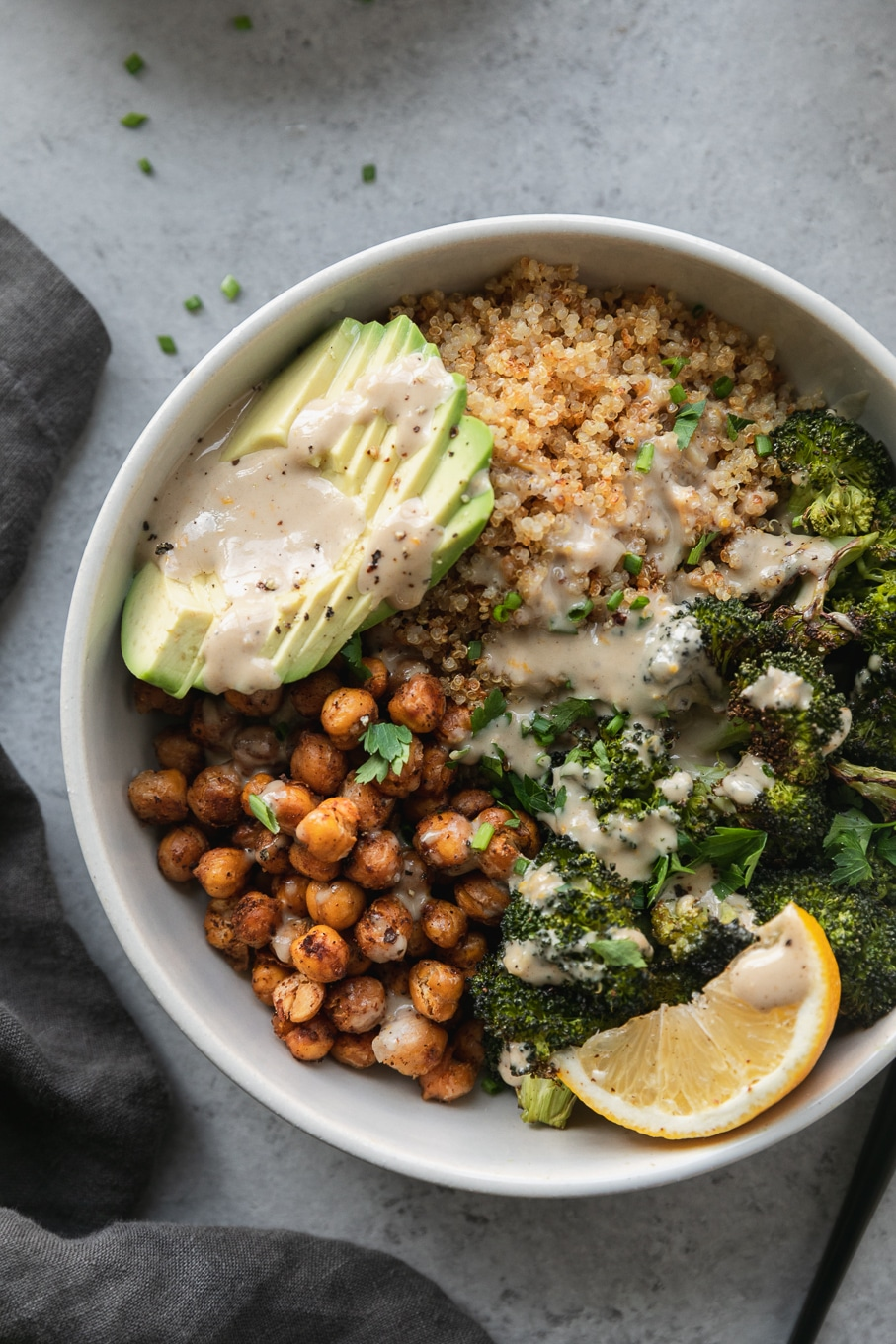 Overhead close up shot of a bowl with chickpeas, sliced avocado, quinoa, roasted broccoli, tahini sauce, and a lemon wedge with a dark grey linen next to it