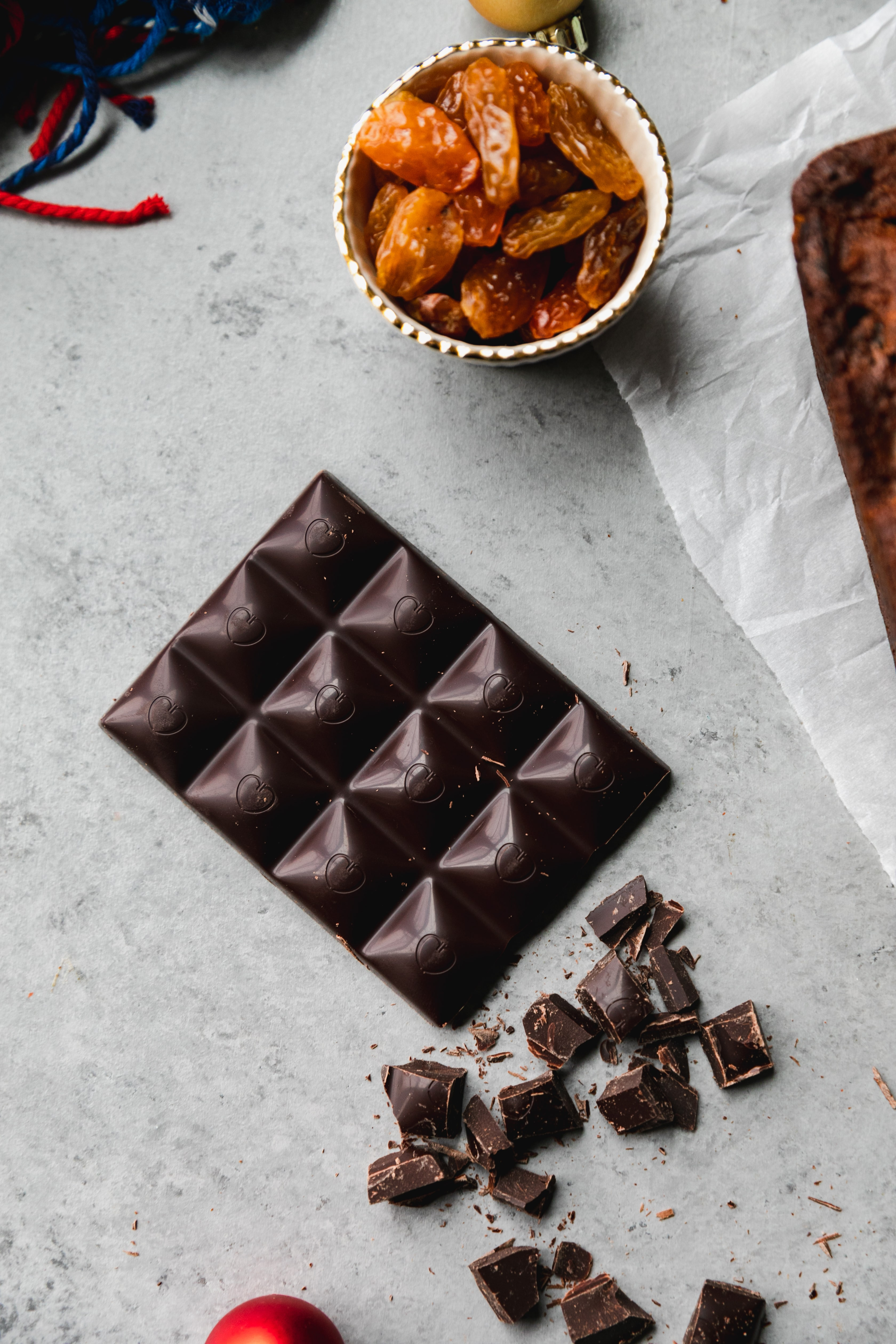 Overhead shot of a bar of dark chocolate and chopped dark chocolate against a grey background