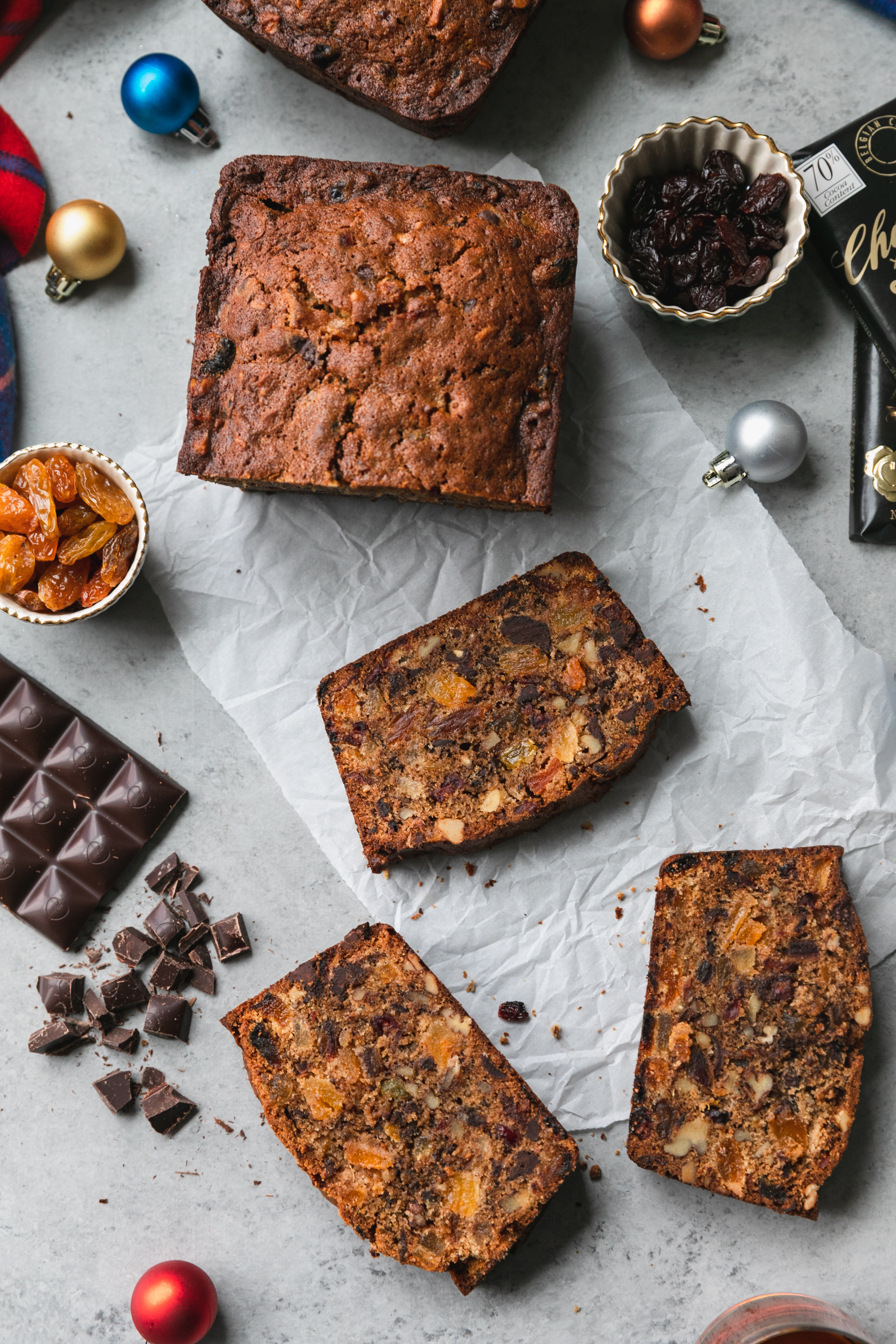Overhead shot of a fruitcake loaf and fruitcake slices with chopped dark chocolate and ornaments scattered around