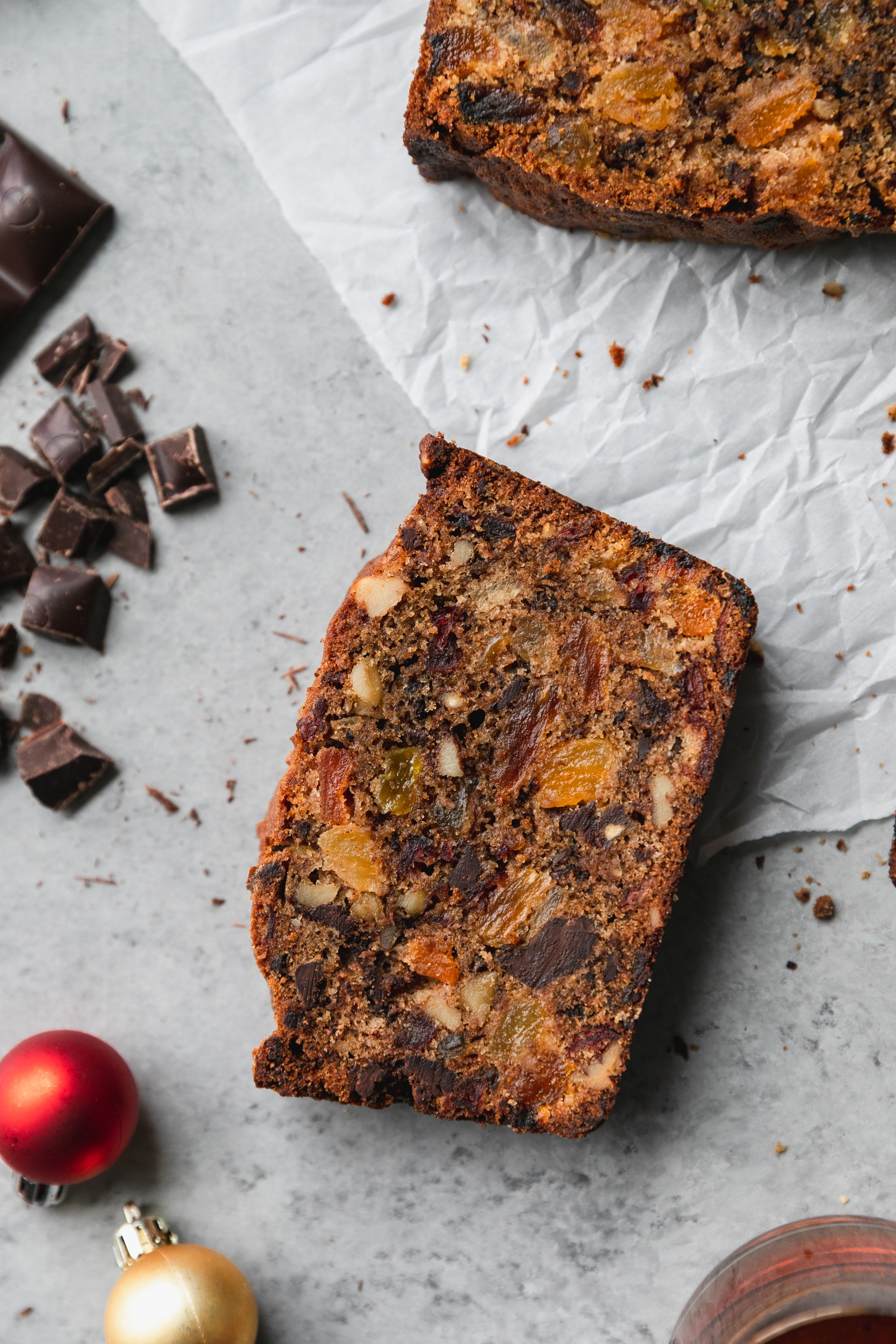 Overhead close up shot of a slice of fruitcake on a grey background with chopped dark chocolate and a red ornament scattered around