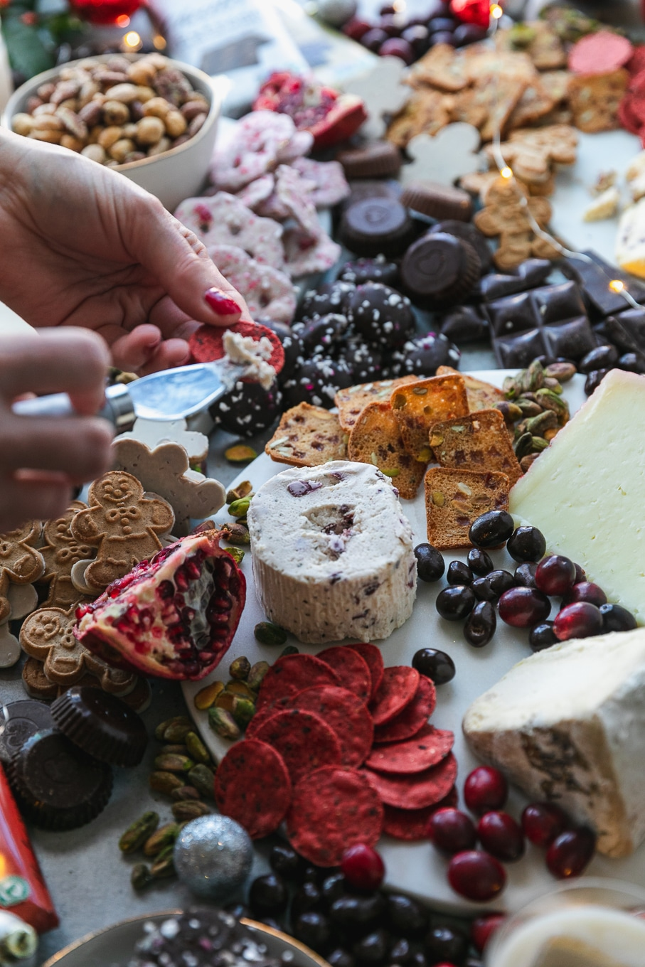 Close up shot of a cheeseboard surrounded by chocolate and treats, with hands spreading some cheese on a cracker