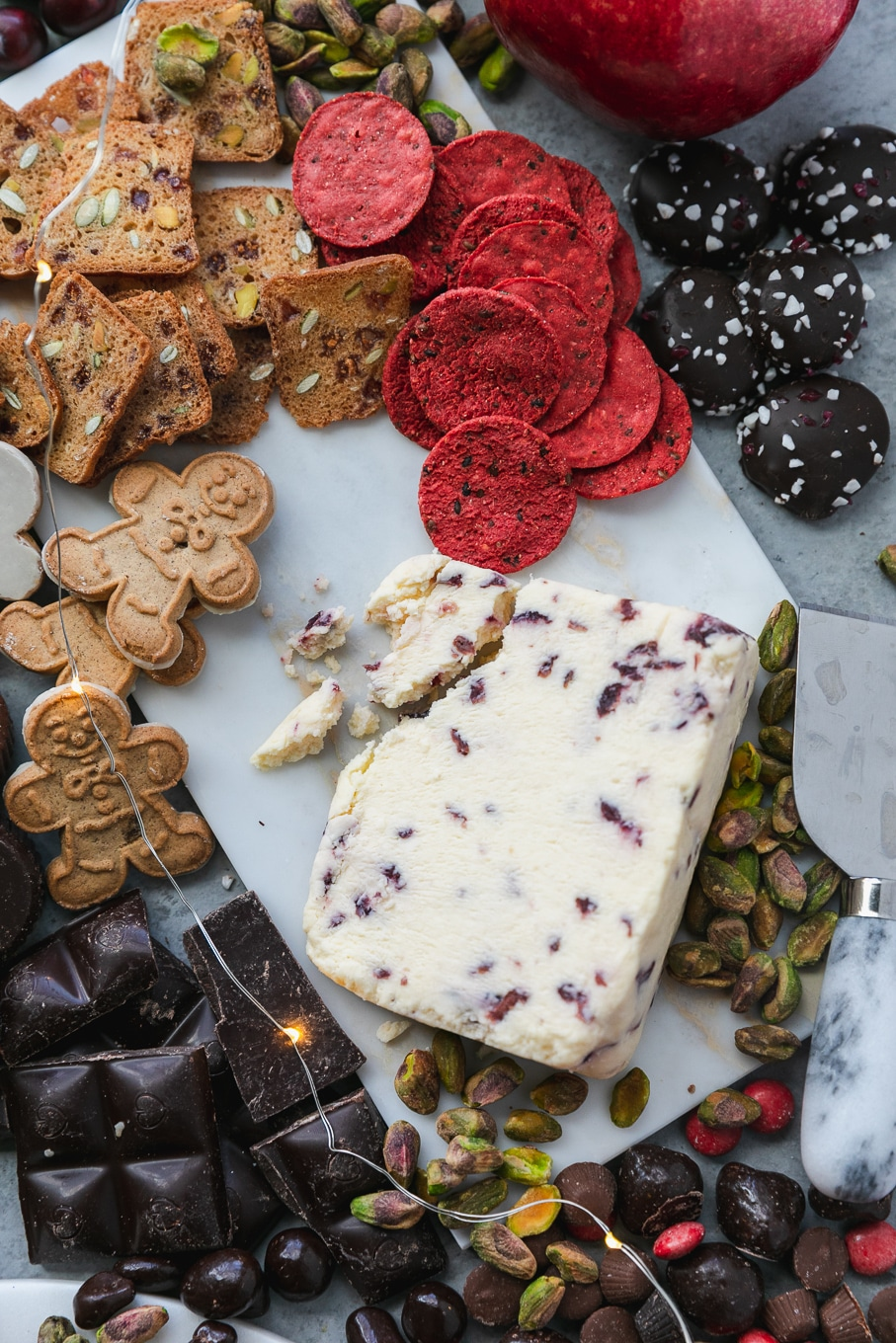 Overhead shot of a cranberry cheese surrounded by red crackers, gingerbread men, pistachios, peppermint chocolate candies, and a dark chocolate bar