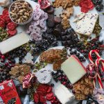 Overhead shot of a chocolate and cheeseboard filled with cookies, chocolate bars, crackers, cheeses, pomegranate, chocolate covered pretzels, candy canes, and assorted nuts