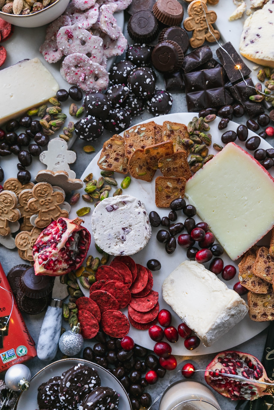 Overhead shot of a chocolate and cheeseboard filled with cookies, chocolate bars, crackers, cheeses, pomegranate, and assorted nuts