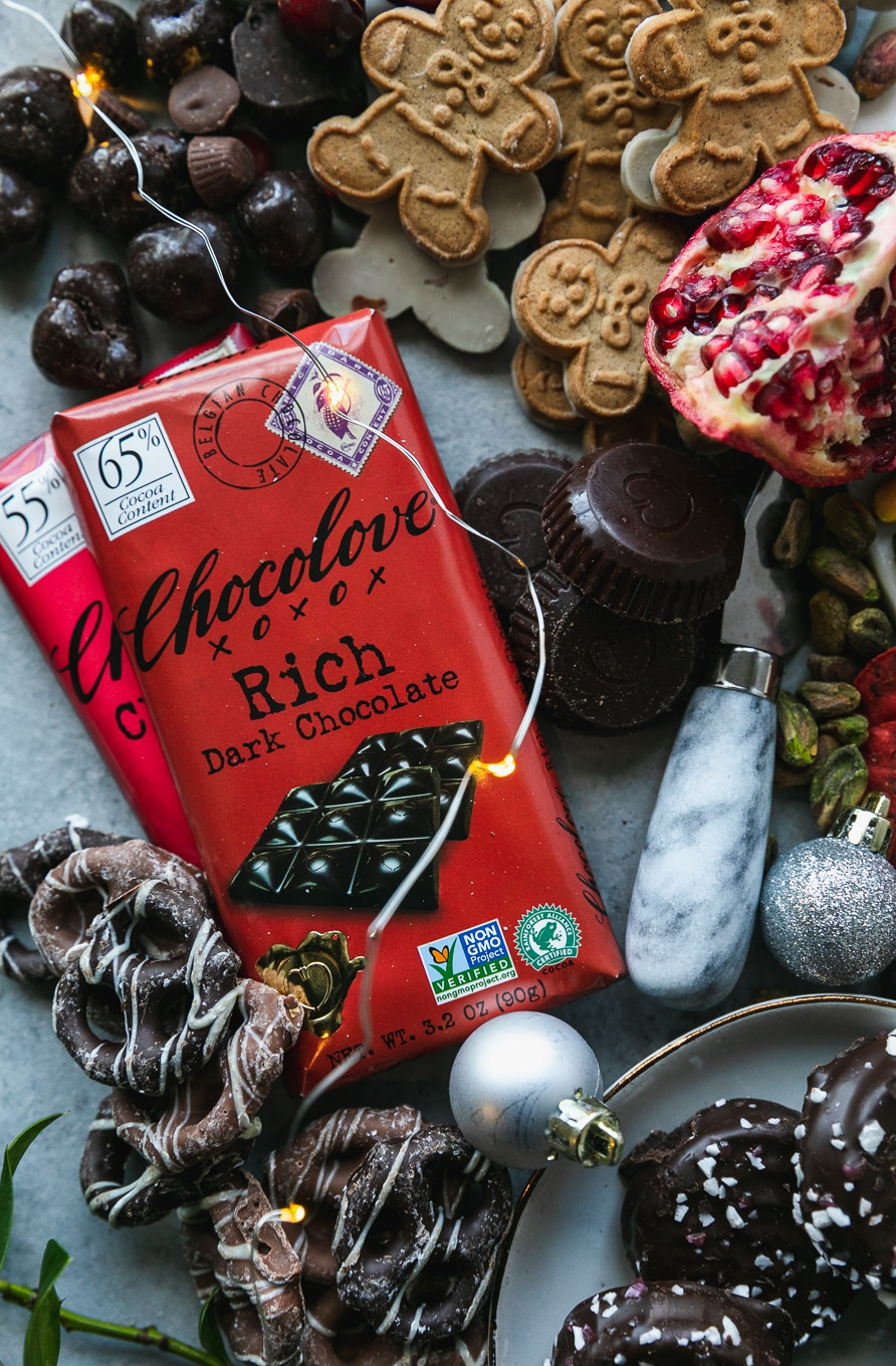 Overhead shot of two chocolate bars wrapped in a red wrapper surrounded by chocolate covered pretzels, chocolate, and gingerbread men cookies
