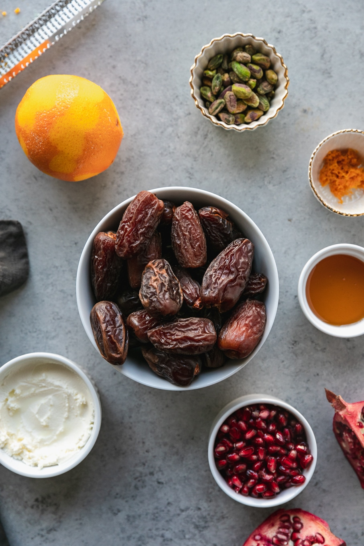 Overhead shot of a bowl of dates surrounded by ramekins of orange zest, honey, pomegranate arils, pistachios, and mascarpone
