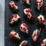 Overhead shot of mascarpone stuffed dates topped with pomegranate arils on a black background